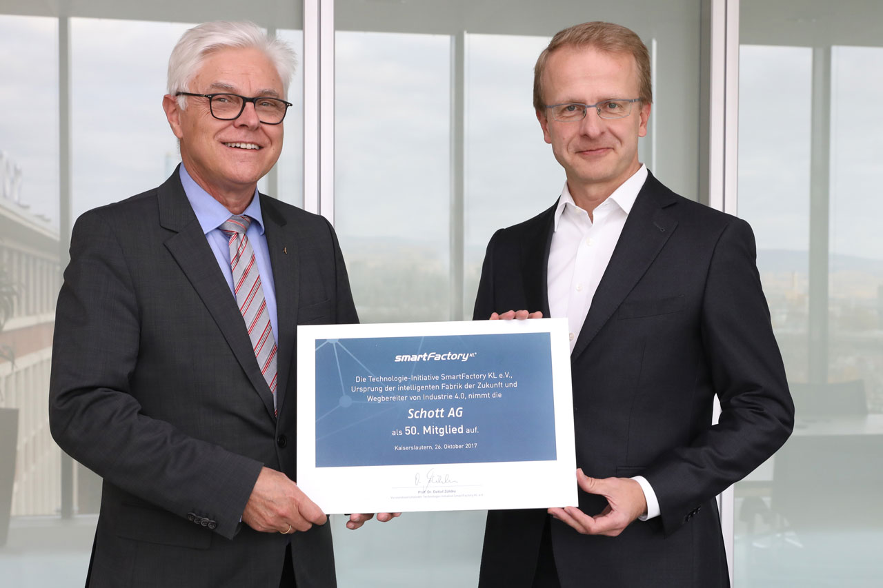Prof. Dr. Detlef Zühlke (SmartFactoryKL) is handing over the membership document to Prof. Jens Schulte (Schott AG). Foto: A.Sell