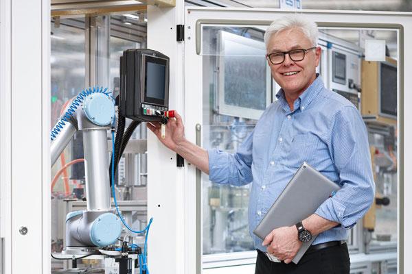 Prof. Dr. Detlef Zühlke im Vordergrund der Industrie 4.0-Anlage