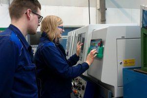 Auszubildende bei der Anwendung von AmbiWise an einer Arbeitsstation. Foto: Daimler AG.