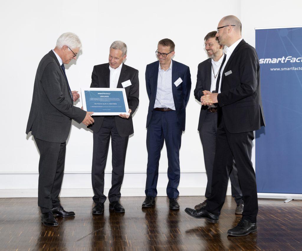 Prof. Dr. Detlef Zühlke erhält eine Urkunde bei der Ernennung zum Ehrenmitglied des Vorstands. Foto: SmartFactory-KL/M. Schäfer